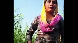 Desi beauty removing clothing in field.
