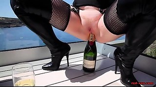 Aged Red XXX copulates a champagne bottle outside